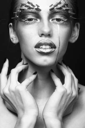 animal sexy: Closeup portrait of one beautiful sexy wild young woman with bright animal makeup with thorns on face in studio black and white, vertical picture