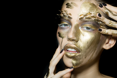 wildlife animal: Closeup portrait of one beautiful sexy wild young woman with bright golden animal makeup with thorns on face in studio on black background, horizontal picture Stock Photo