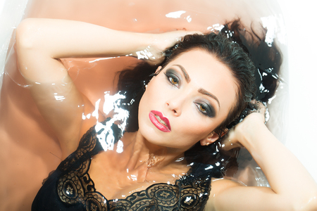 sensory: Closeup portrait of one sexual young sensory passionate attractive brunette woman with wet long curly hair and bright makeup lying in bath tab full of water taking shower in cloth, horizontal picture Stock Photo