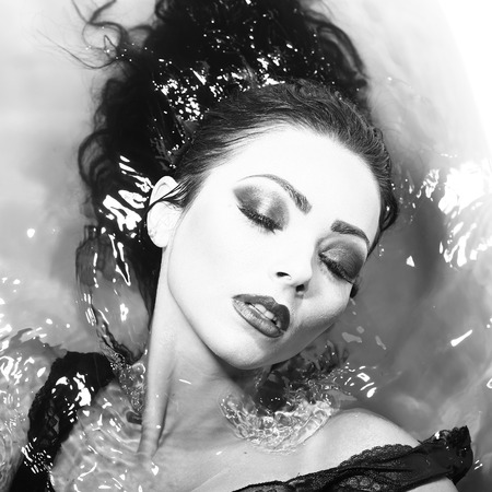sensory: Closeup of one sexual young sensory attractive brunette woman with wet long curly hair and bright makeup lying in bath tab full of water taking shower in cloth black and white, square picture