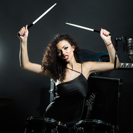 Closeup of one beautiful emotional expressive cool young brunette sexual rock musician woman with long curly hair standing in recording studio playing drums with sticks near electro guitar and microphone