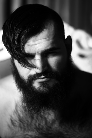 hairy chest: Closeup portrait of one handsome serious young adult man with long lush beard and stylish hairdo with bare haired chest looking forward indoor on blurred backdrop black and white, vertical picture