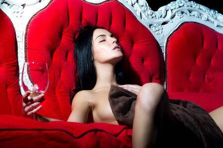 modelos desnudas: Una morena desnuda joven glamour pensativo sexual con el pelo largo que se sienta con la copa de vino en el estudio de interior en el sofá rojo clásico deseando en el fondo brillante, cuadro horizontal