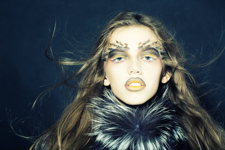 animal hair: Closeup portrait of one beautiful wild young woman with bright golden animal monkey makeup with thorns on face in fur coat on black background, horizontal picture Stock Photo
