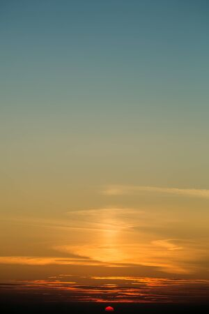 surrealistic: Photo beautiful evening view of surrealistic spectacular orange colorful sunset with half of bright sun below horizon on peaceful clear blue sky background, vertical picture