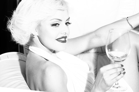 monroe: One attractive sensual smiling sexy young retro woman with blonde hair bright lips in dress in monroe style indoor drinking glass of wine sitting in chair black and white, horizontal picture Stock Photo