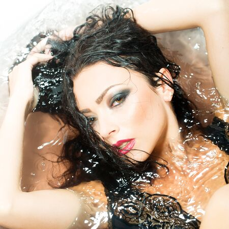 lying in bathtub: Closeup portrait of one sexual young sensory passionate attractive brunette woman with wet long curly hair and bright makeup lying in bath tab full of water taking shower in cloth, square picture