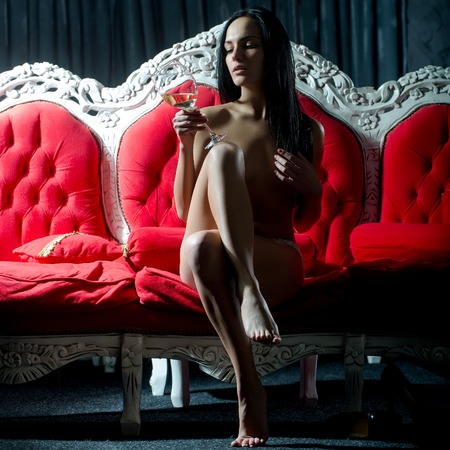 sexual nude: One beautiful sexual naked brunette young woman with straight slim body and long hair holding wine glass sitting indoor in studio on red classic couch on dark background, square picture Stock Photo