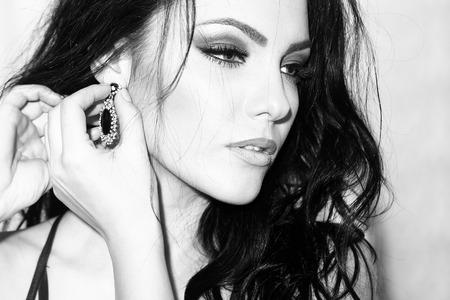 modelos posando: Retrato de una mujer sexual joven hermosa con el pelo rizado cuerpo recto delgado y maquillaje brillante en elegante vestido poner en la joyería de pie en el oído interior en blanco y negro, cuadro horizontal Foto de archivo