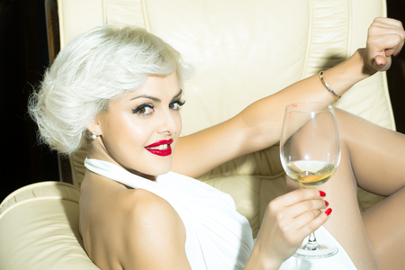 monroe: Closeup portrait of one attractive sensual smiling sexy young retro woman with blonde hair red lips in white dress in monroe style indoor drinking glass of wine sitting in chair, horizontal picture