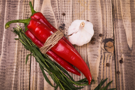 poignant: Bright red chili hot peppers tied by rope white clean garlic branches of eating herb spicy allspice vegetable harvest in autumn healthy lifestyle on wooden background studio top view, horizontal