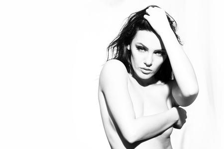 mujeres negras desnudas: Retrato del primer de una linda joven sensual mujer sexy desnuda con el pelo largo y rizado y maquillaje brillante celebración de la mano cerca de la cara de pie en interiores ganas blanco y negro, imagen horizontal