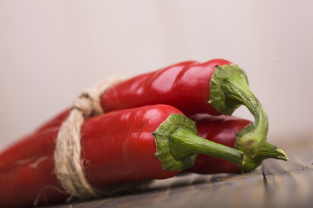 poignant: Vegetarian natural fiery ingredient condiment ripe red poignant cayenne pepper vegetable tied by rope lying on wooden table indoor on light background closeup, horizontal picture