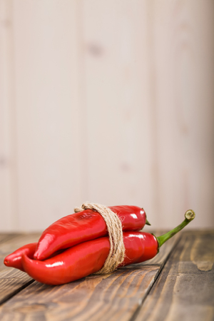 poignant: Healthy ingredient plant for pungent maxican food vibrant red domestic chile peppers tied with brown rope laying on wooden table on light background studio closeup copyspace, vertical picture