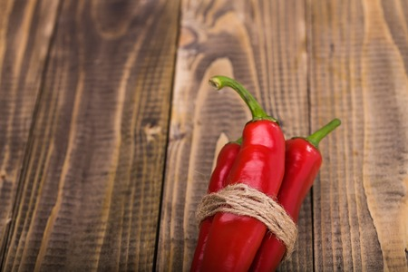pungent: Bunch of red pungent chili peppers with green tails tied by rope natural eco ingredient on wooden background closeup copyspace, horizontal picture