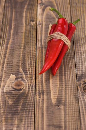 piquant: Ripe burning eating organic vegetarian ingredient condiment pod peppers cayenne tied by rope cooking piquant food on wooden background closeup copyspace studio, vertical picture