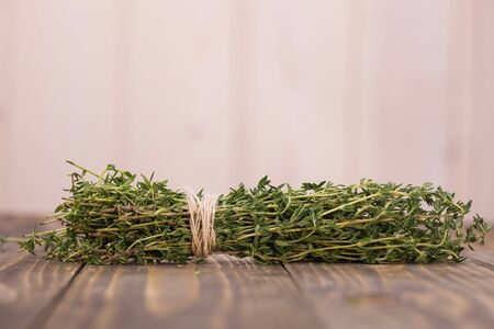 herbal background: Bunch of fragrant rosemary branches herb tied by twine herbal ingredient for medicine aromatherapy healthy lifestyle object laying on wooden table on light background closeup copyspace, horizontal