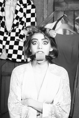 haircurlers: Closeup of one cute young fashionable emotional surprised woman in dressing gown with hair-rollers on head and in mouth standing in wardrobe among many bright clothes black and white, vertical picture Stock Photo