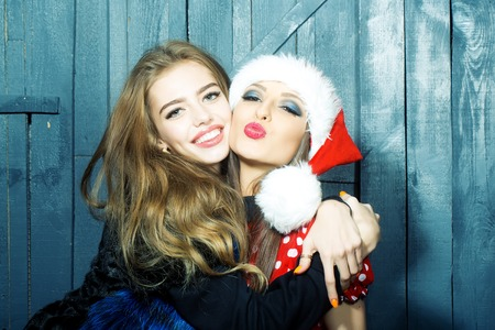 christmas costume: Closeup view of two beautiful brunette young happy smiling embracing new year women celebrating christmas in red santa claus hat with white fur holding gift box indoor, horizontal picture