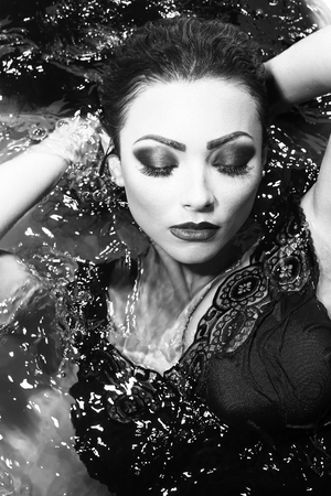 sensory: Closeup of one sexual young sensory attractive brunette woman with wet long curly hair and bright makeup lying in bath tab full of water taking shower in cloth black and white, vertical picture