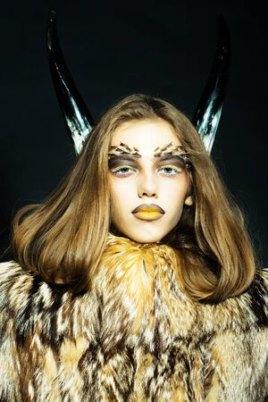 woman in fur coat: Closeup portrait of one beautiful wild young woman with bright golden animal monkey makeup with thorns on face and antlers in fur coat on black background, vertical picture Stock Photo