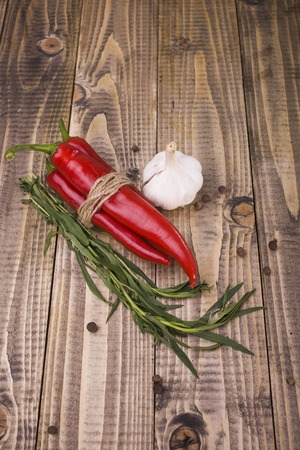 savour: Set of cuisine natural organic eco products ingredient for tasty piquant dish with piquant savour allspice tied by rope red raw chili peppers ripe aromatic garlic studio on wooden background, vertical