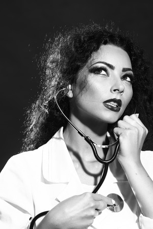 Closeup view portrait of one sexy beautiful brunette medical worker with positive emotions holding stethoscope in white nurse uniform in studio black and white, vertical picture