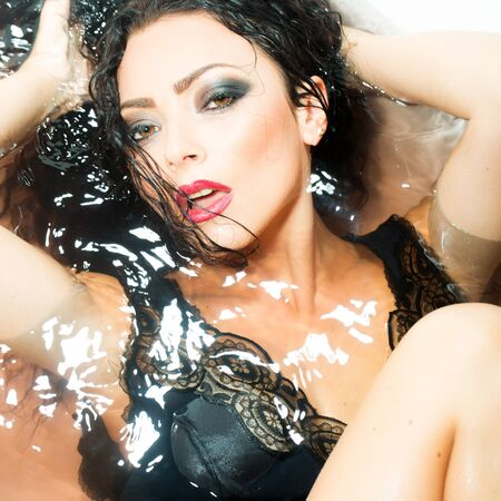 taking shower: Closeup portrait of one sexual young sensory passionate attractive brunette woman with wet long curly hair and bright makeup lying in bath tab full of water taking shower in cloth, square picture