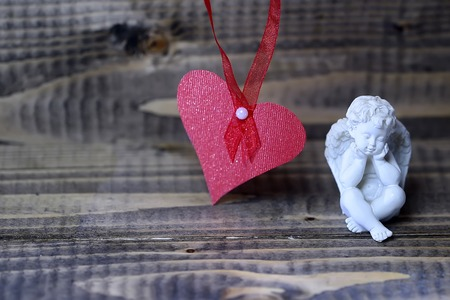 putto: Closeup view of one beautiful cupid angel decorative figurine near red paper greeting valentine card on hanging ribbon with no people on wooden background copy space, horizontal picture