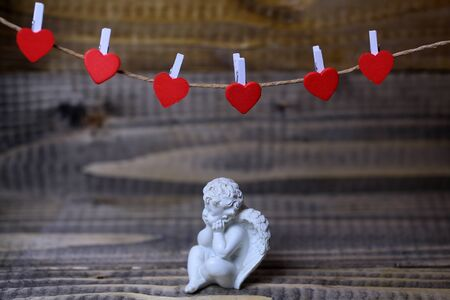 clothespeg: Closeup view of one beautiful cupid angel decorative figurine near red clothes-peg in shape of heart with no people on wooden background, horizontal picture Stock Photo