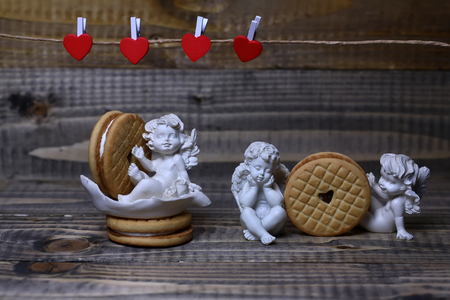 putto: Closeup view of beautiful cupid angels decorative figurine near red paper greeting valentine clothes-peg in shape of heart with round pastry on wooden background, horizontal picture