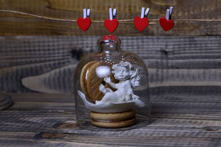 clothespeg: Closeup view of beautiful cupid angel decorative figurine near red paper greeting valentine clothes-peg in shape of heart with round pastry under glass flask on wooden background, horizontal picture