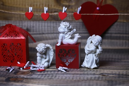 clothespeg: Closeup view of few beautiful cupid angels decorative figurine near red paper greeting valentine box and card on hanging ribbon on clothes-peg with no people on wooden background, horizontal picture