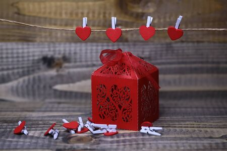 clothespeg: Closeup view of one beautiful decorative red paper greeting valentine box with ribbon bow near hanging clothes-peg in shape of heart with no people on wooden background, horizontal picture