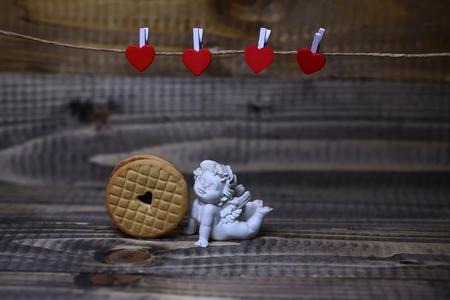 clothespeg: Closeup view of beautiful cupid angel decorative figurine near red paper greeting valentine clothes-peg in shape of heart with round pastry on wooden background copy space, horizontal picture Stock Photo