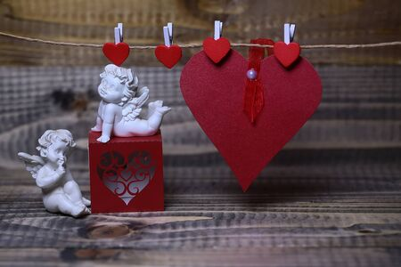putto: Closeup of few beautiful cupid angels decorative figurine near red paper greeting valentine box and card on hanging ribbon on clothes-peg with no people on wooden background copy space, horizontal