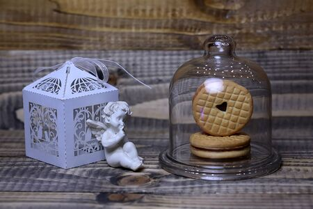 clothespeg: Closeup of beautiful cupid angel decorative figurine near white paper greeting valentine box and red hanging clothes-peg with round cookie under glass flask on wooden background, horizontal picture Stock Photo