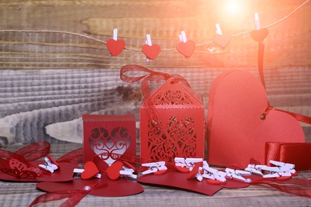 clothespeg: Closeup of beautiful decorative red paper valentine boxes with ribbon bow near greeting cards hanging clothes-peg in shape of heart with no people on wooden background copy space, horizontal picture