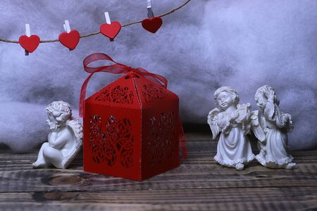 wadding: Closeup view of three beautiful cupid angels decorative figurine near red paper greeting valentine box and hanging clothes-peg in shape of heart with white wadding decorating snow, horizontal picture
