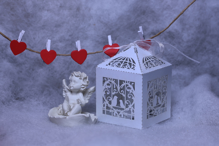 wadding: Closeup view of one beautiful cupid angel decorative figurine near paper greeting valentine box and hanging red clothes-peg in shape of heart with white wadding decorating snow, horizontal picture