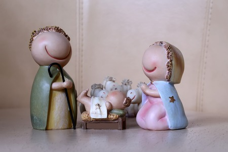 Mother Mary: Closeup view of decorative celbrating Christmas and Jesus birth figurines of holy vergin Mary Josepd newborn child with few white sheeps standing on light leather background, horizontal picture Stock Photo