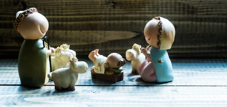 jesus mary joseph: Closeup view of decorative celbrating Christmas and Jesus birth figurines of holy vergin Mary Josepd newborn child with few white sheeps standing on wooden background, horizontal picture