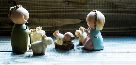 nacimiento de jesus: Vista de cerca de celbrating decorativos de Navidad y Jes�s figurillas de nacimiento de vergin santa Mar�a Josepd ni�o reci�n nacido con pocas ovejas blancas de pie en el fondo de madera, cuadro horizontal
