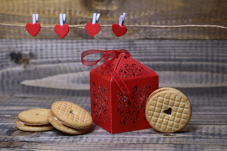 clothespeg: Closeup view of beautiful decorative red paper greeting valentine box with ribbon near clothes-peg in shape of heart with round pastry on wooden background, horizontal picture