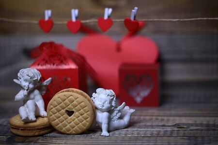 putto: Closeup view of beautiful cupid angels decorative figurine near red paper greeting valentine box near clothes-peg in shape of heart with round pastry on wooden background, horizontal picture Stock Photo