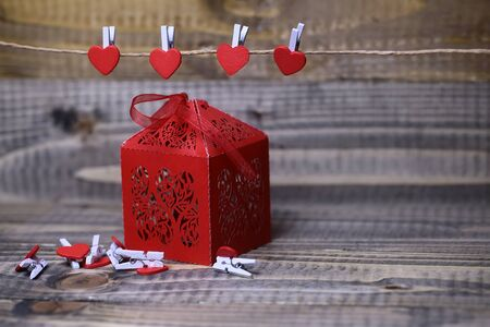 clothespeg: Closeup view of one beautiful decorative red paper greeting valentine box with ribbon bow near hanging clothes-peg in shape of heart with no people on wooden background copy space, horizontal picture Stock Photo