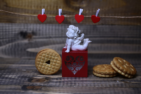 clothespeg: Closeup view of beautiful cupid angel decorative figurine on red paper greeting valentine box near clothes-peg in shape of heart with round pastry on wooden background, horizontal picture