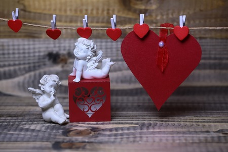 Closeup of few beautiful cupid angels decorative figurine near red paper greeting valentine box and card on hanging ribbon on clothes-peg with no people on wooden background copy space, horizontal
