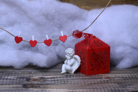 wadding: Closeup view of one beautiful cupid angel decorative figurine near red paper greeting valentine box and hanging clothes-peg in shape of heart with white wadding decorating snow, horizontal picture Stock Photo