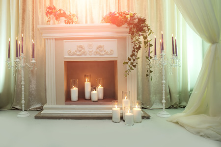 cutglass: Photo elegant fireplace decorated with fresh colorful flowers green leaves two candlesticks with violet candles crystal strings on sides candle lights on white indoor background, horizontal picture
